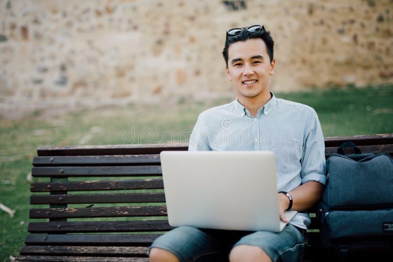 有膝上型计算机笔记本的微笑的亚裔人坐在s的长凳 免版税库存照片