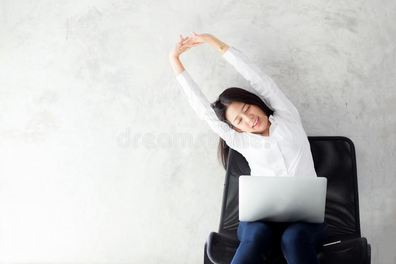 有膝上型计算机舒展的美丽的年轻亚裔妇女和锻炼在工作成功以后放松 图库摄影