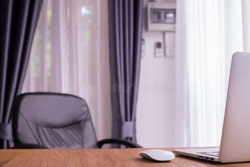 有膝上型计算机,笔记本后面的办公桌在屋子里 免版税库存照片