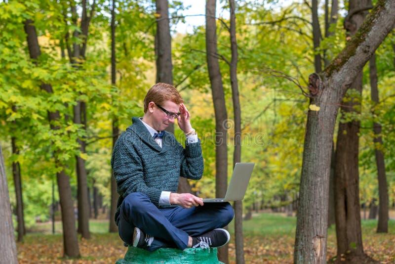有膝部上面的一个人在秋天公园假装是一个雕象的垫座 有想法 库存照片