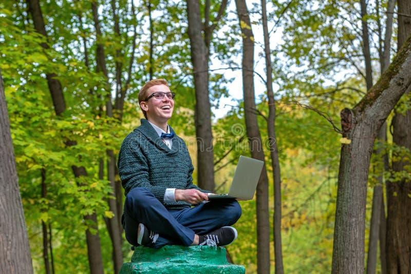 有膝部上面的一个人在秋天公园假装是一个雕象的垫座 有想法 免版税图库摄影
