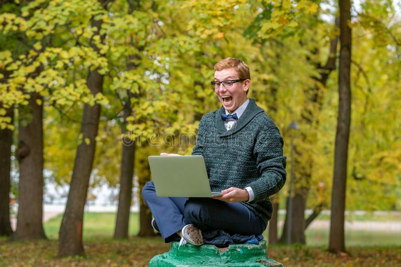 有膝部上面的一个人在秋天公园假装是一个雕象的垫座 有想法 免版税库存图片