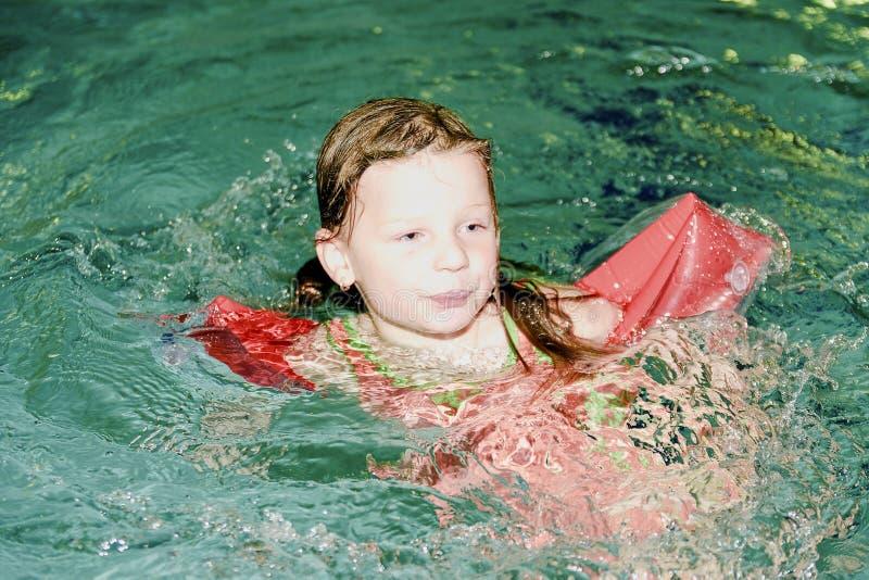 有臂章的小白肤金发的女孩在游泳池漂浮 孩子学会对swimm 免版税图库摄影