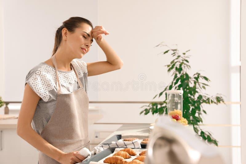 有自创烤箱的疲倦的妇女烘烤了酥皮点心 库存照片