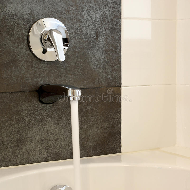 有自来水的浴缸从龙头 库存图片