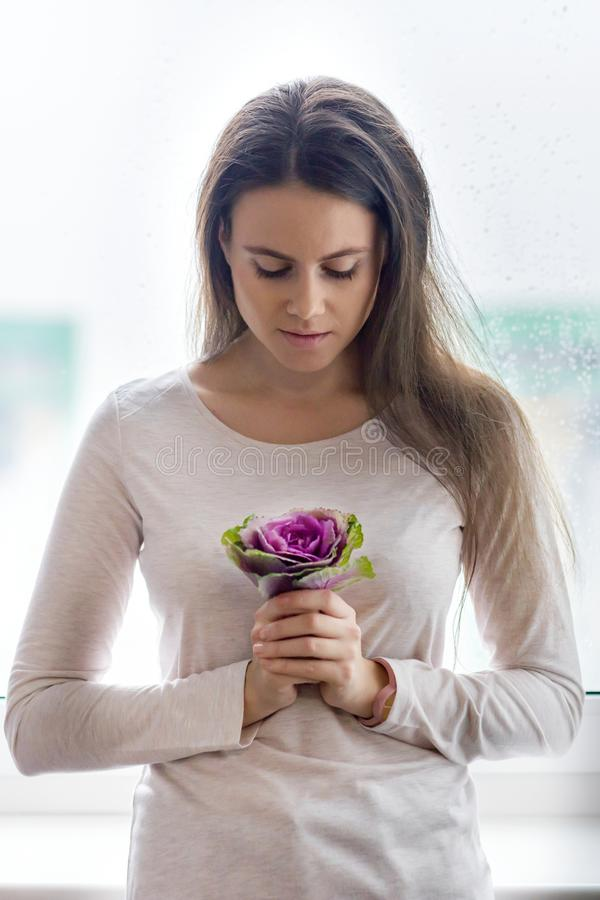 有自然构成,长和健康棕色头发的年轻美女 女孩用在窗口附近的紫色花卉花圆白菜 Co 库存照片