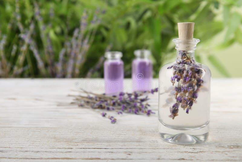 有自然草本油和淡紫色的瓶在桌上开花反对被弄脏的背景 免版税库存图片
