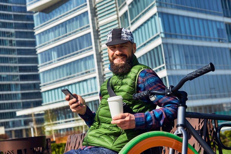 有自行车和智能手机的一个年轻人基于一条长凳在城市 免版税图库摄影