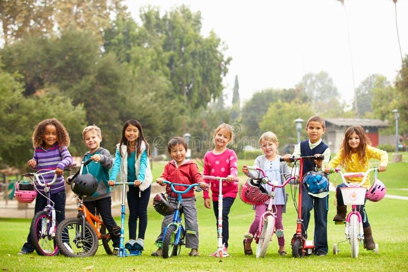 有自行车和滑行车的幼儿在公园 免版税图库摄影