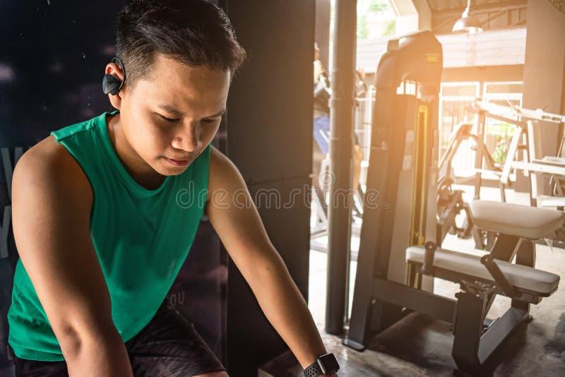 有自行车机器的亚裔人爱好健美者衡量力量handsom 库存照片
