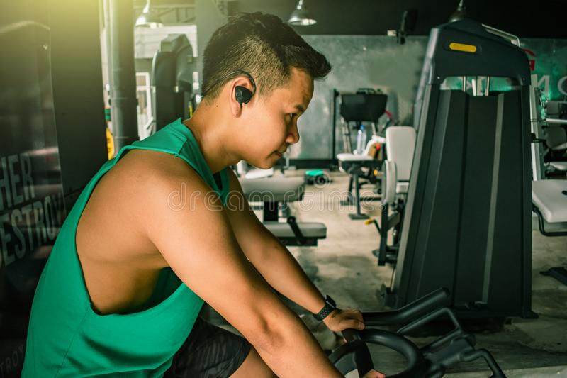 有自行车机器的亚裔人爱好健美者衡量力量handsom 免版税库存图片