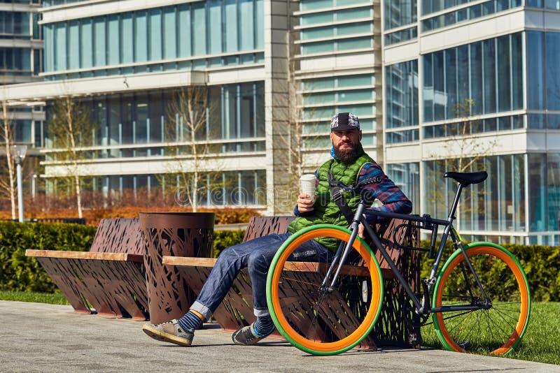 有自行车的一个年轻人在城市拿着一杯咖啡,基于一条长凳 免版税库存照片