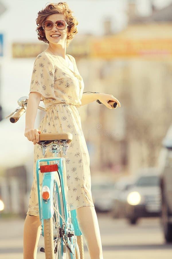 有自行车的女孩在日落夏天城市 免版税库存图片