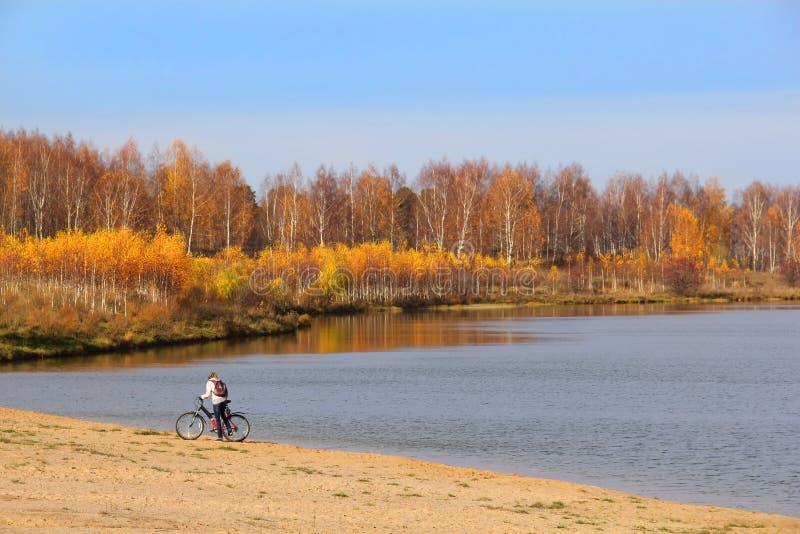 有自行车的女孩在湖边 免版税图库摄影