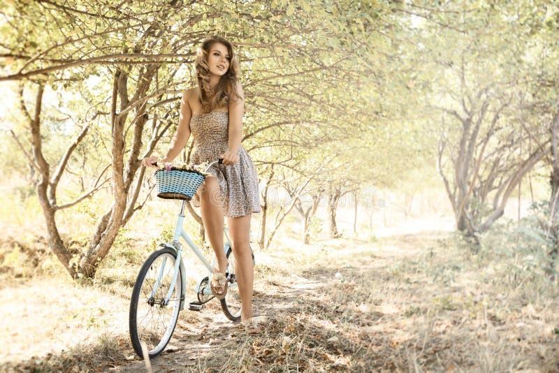 有自行车的少妇在公园 免版税库存图片