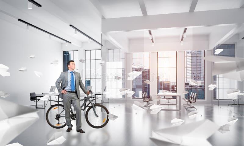 有自行车的年轻人佩带的西装 免版税库存图片