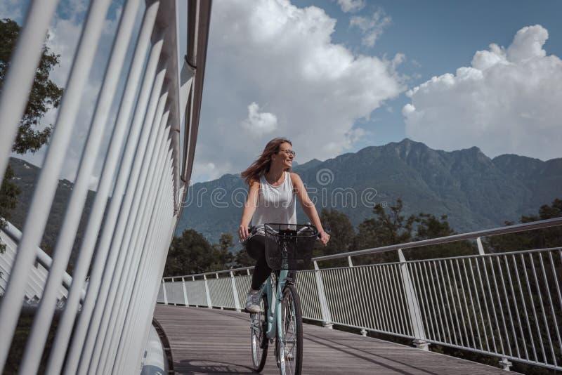 有自行车的年轻可爱的妇女在桥梁 免版税库存图片