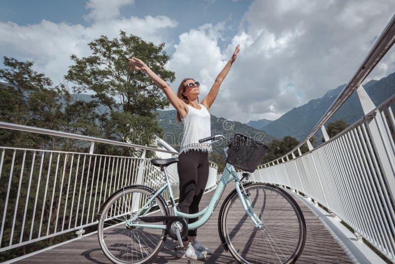 有自行车的年轻可爱的妇女在桥梁 免版税图库摄影