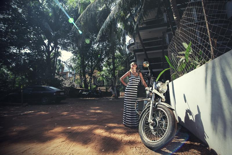有自行车的年轻美丽的愉快的妇女在一条热带亚洲街道上 库存图片