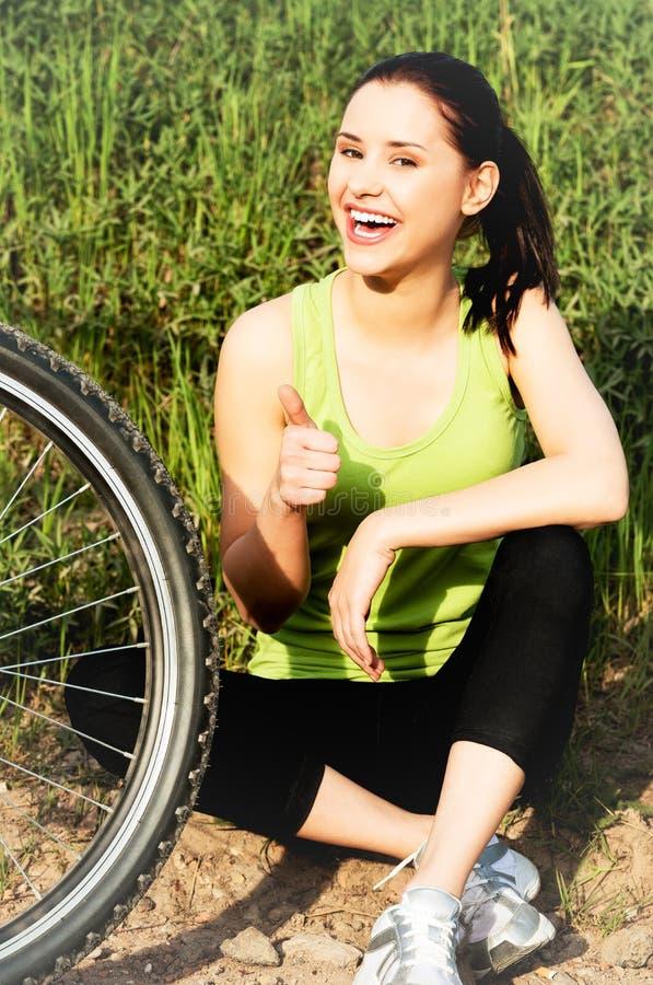 有自行车的微笑的妇女 免版税库存照片
