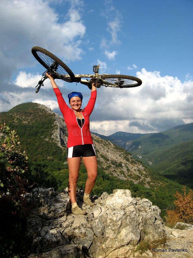 有自行车的微笑的愉快的女孩在山 免版税图库摄影