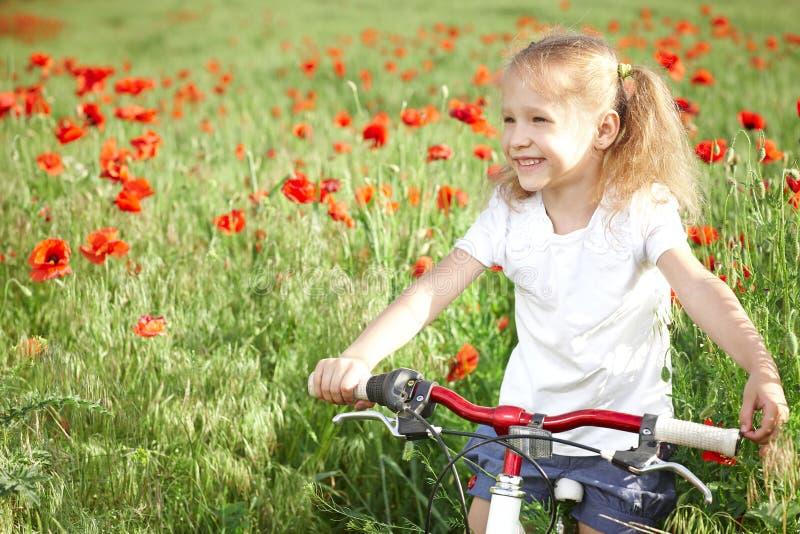 有自行车的愉快的微笑的小女孩 库存图片