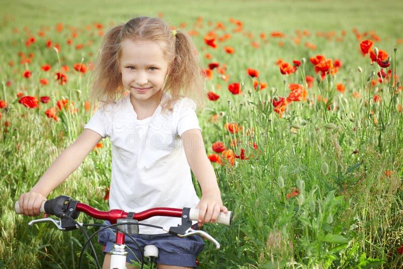 有自行车的愉快的微笑的小女孩 免版税库存照片