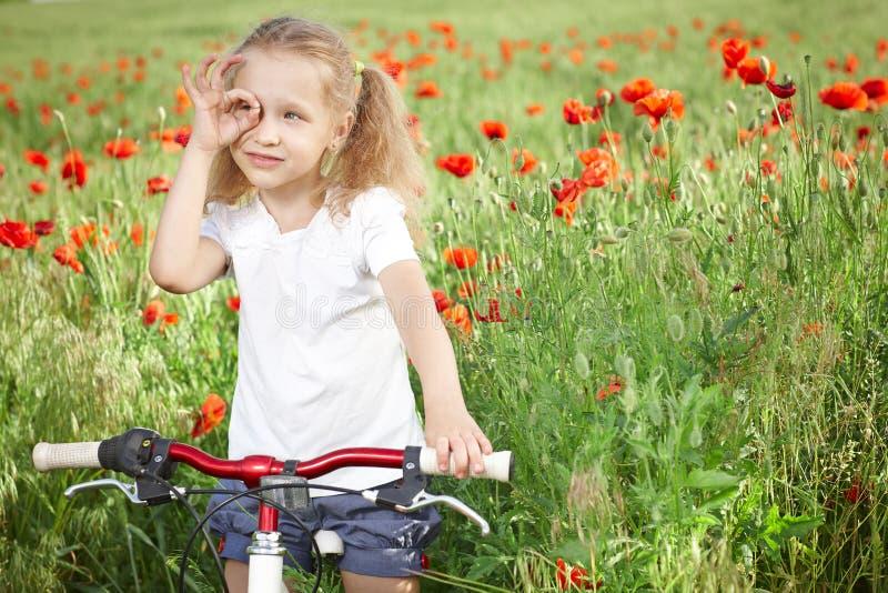 有自行车的愉快的微笑的小女孩 免版税库存图片