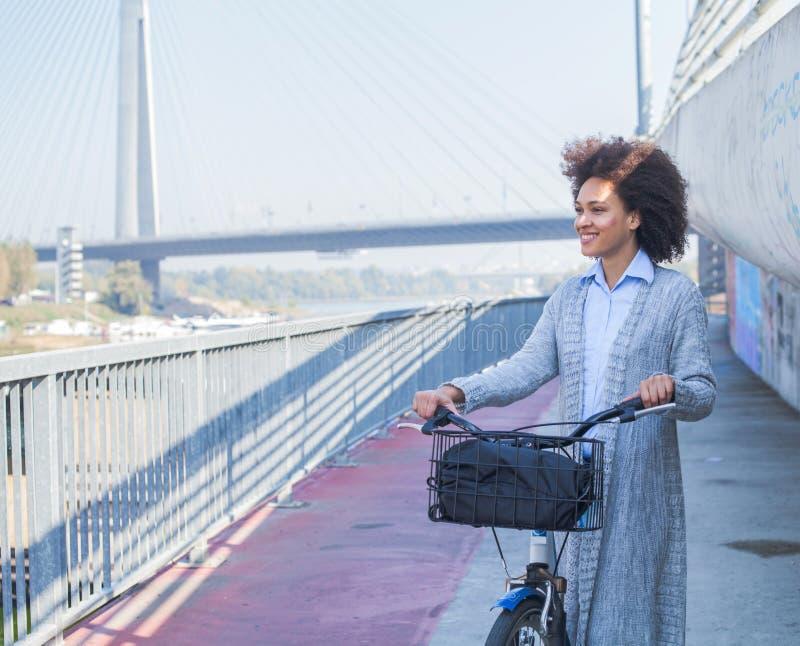 有自行车的愉快的蓬松卷发年轻女人 免版税库存图片