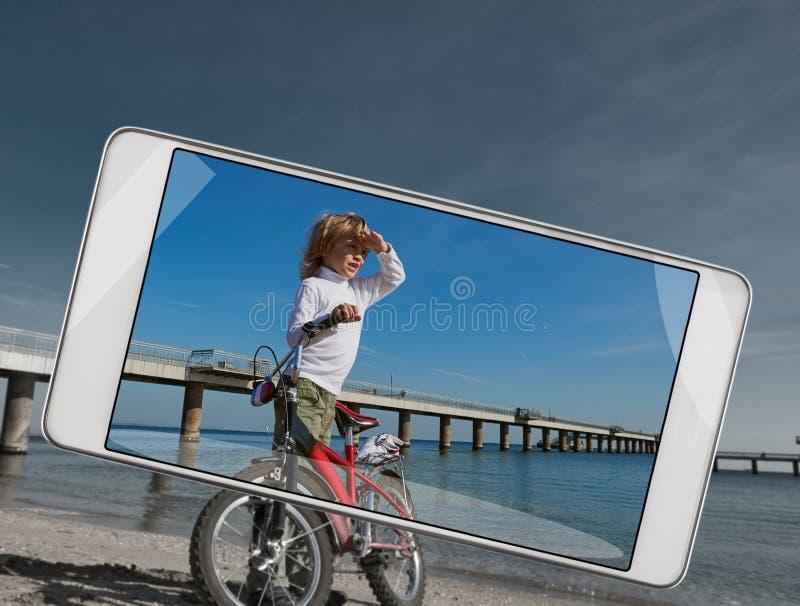 有自行车的男孩在智能手机的海附近 库存照片