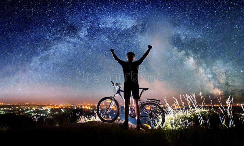 有自行车的骑自行车者夜在满天星斗的天空下 免版税库存图片