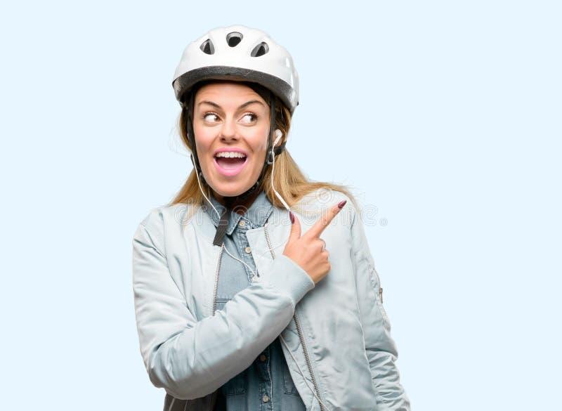 有自行车盔甲的在蓝色背景的少妇和耳机 图库摄影