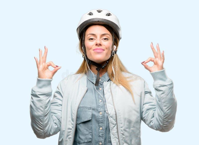 有自行车盔甲的在蓝色背景的少妇和耳机 免版税库存照片