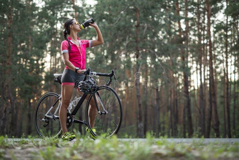有自行车饮料的女孩从烧瓶 免版税库存照片