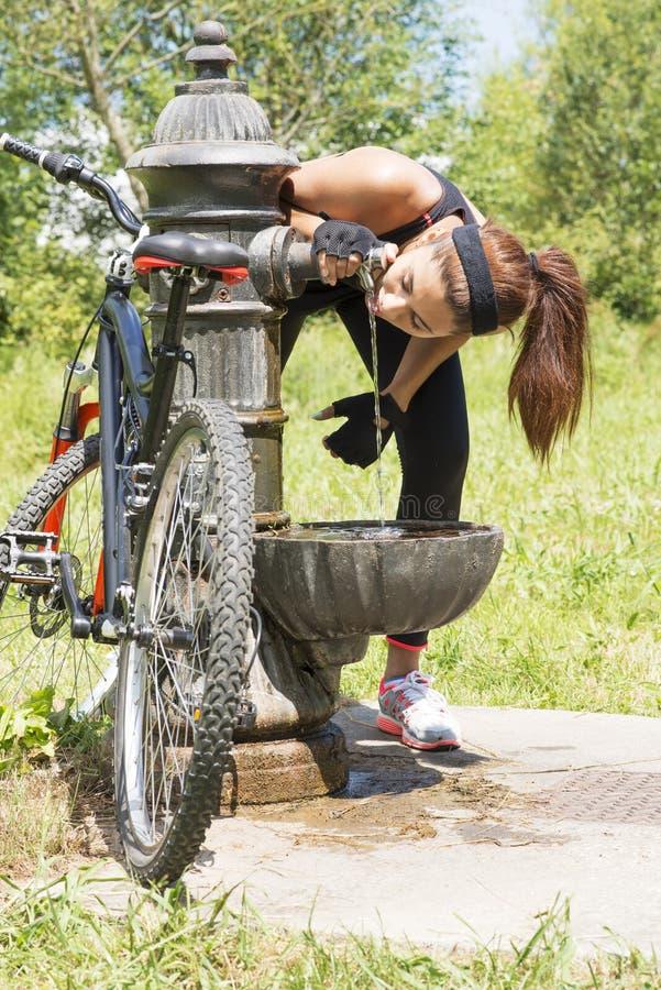 有自行车饮用水的运动妇女在锻炼以后,室外 免版税库存照片