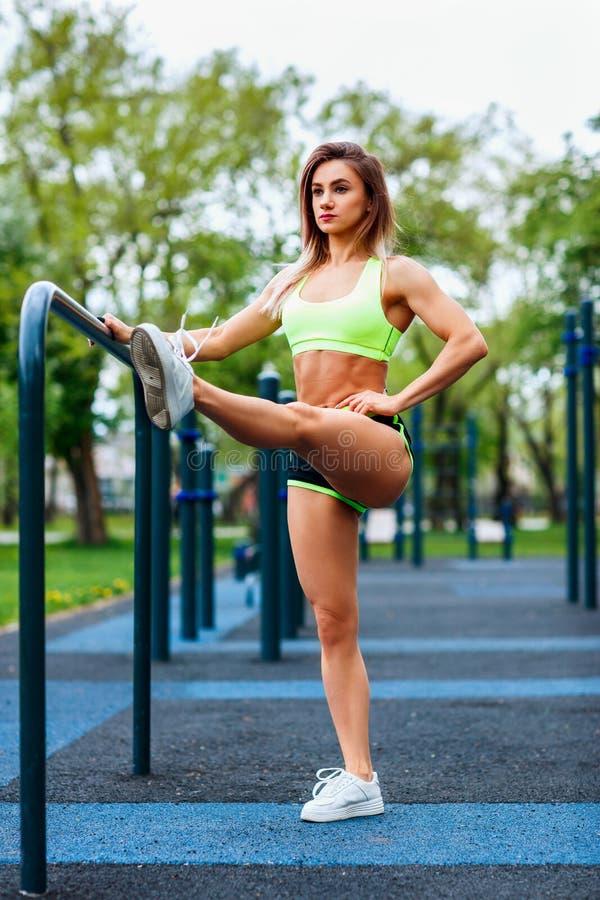 有舒展在公园的完善的运动身体的运动的妇女 免版税库存照片