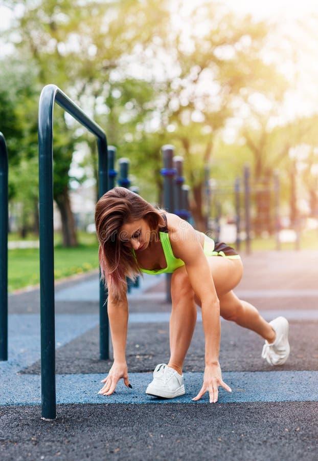有舒展在公园的完善的运动身体的运动的妇女 免版税库存图片