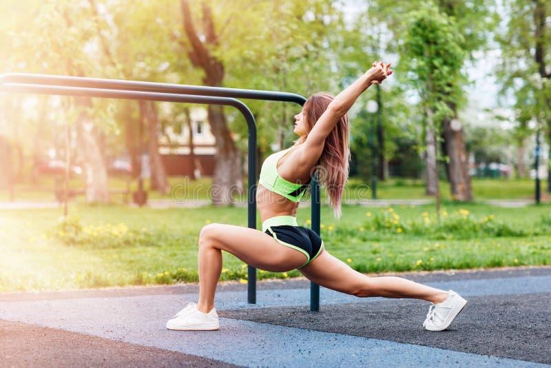 有舒展在公园的完善的运动身体的运动的妇女 免版税图库摄影