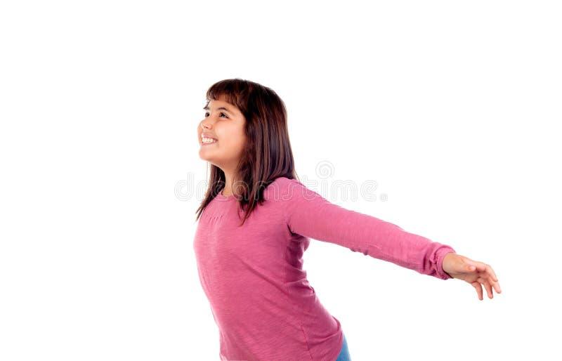 有舒展她的胳膊的桃红色T恤杉的愉快的儿童女孩 免版税库存图片