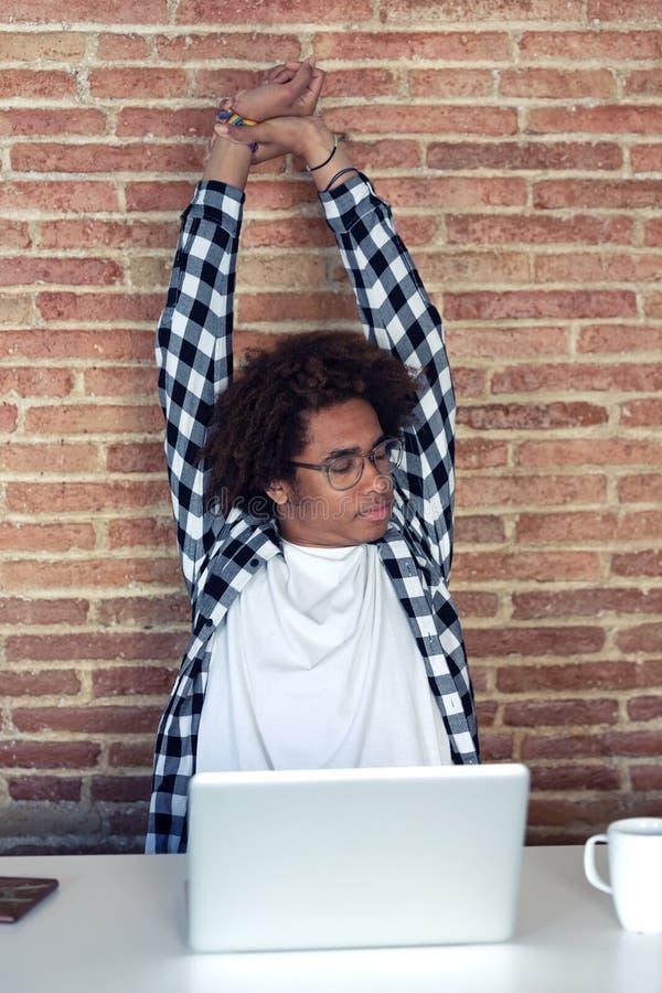 有舒展的镜片的疲乏的年轻美国黑人的人,当在家时与膝上型计算机一起使用 库存照片