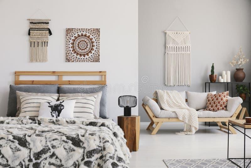 有舒适的加长型的床、典雅的长椅和花边的温暖的ethno卧室在墙壁上 免版税库存图片