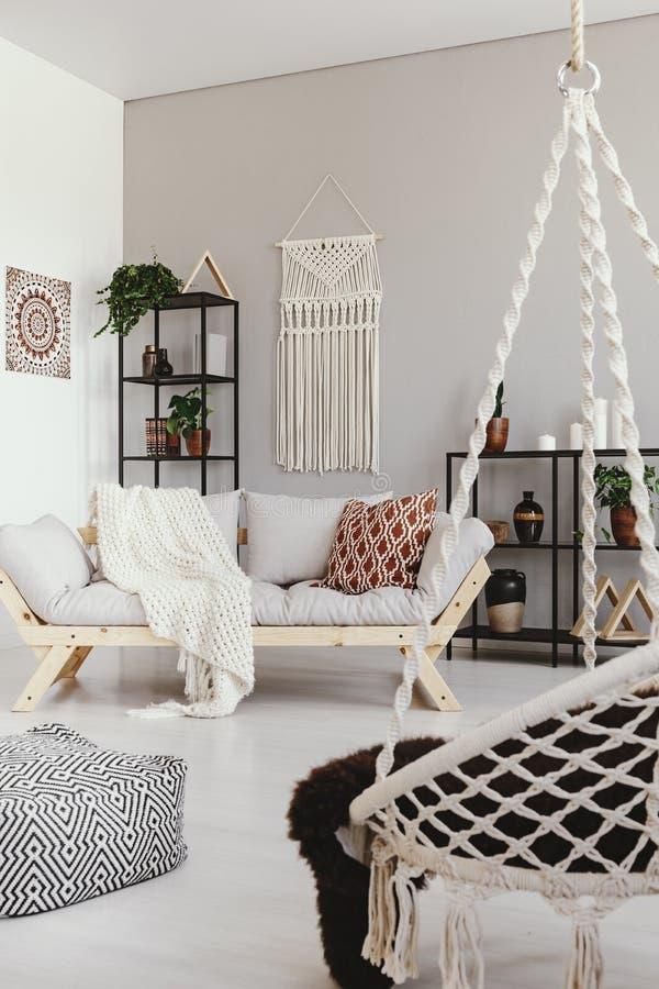 有舒适的长沙发的,真正的照片温暖的ethno客厅 图库摄影