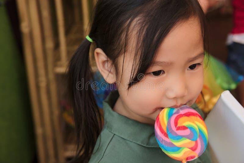 有舔的彩虹棒棒糖亚裔女性小孩 免版税库存照片