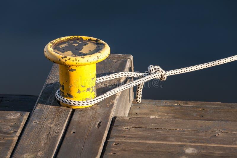 有船舶绳索的黄色停泊系船柱在码头 免版税库存图片