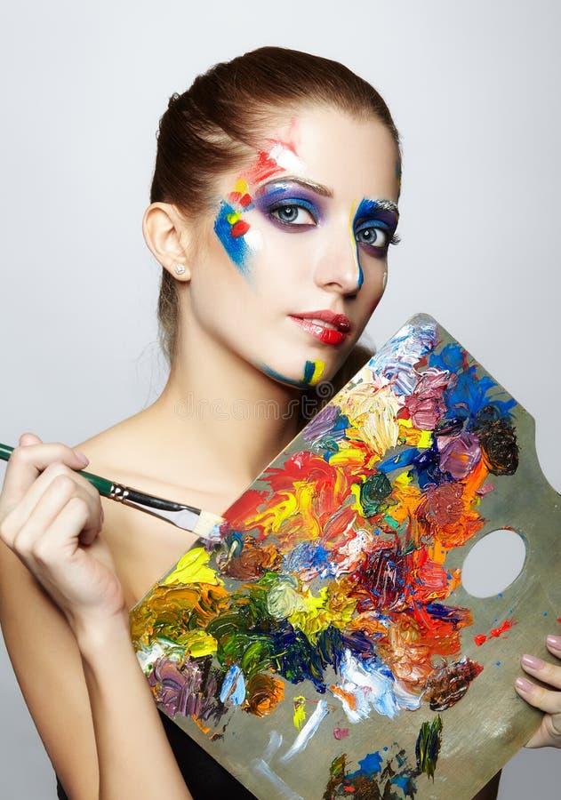 有色板显示和画笔的少妇画家 库存照片