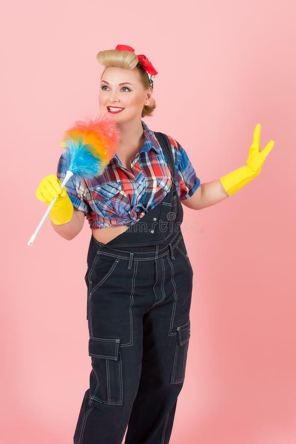 有色的喷粉器唱歌的白肤金发的画报妇女 牛仔布和黄色手套的滑稽的女孩 美国风格画报的概念 库存图片