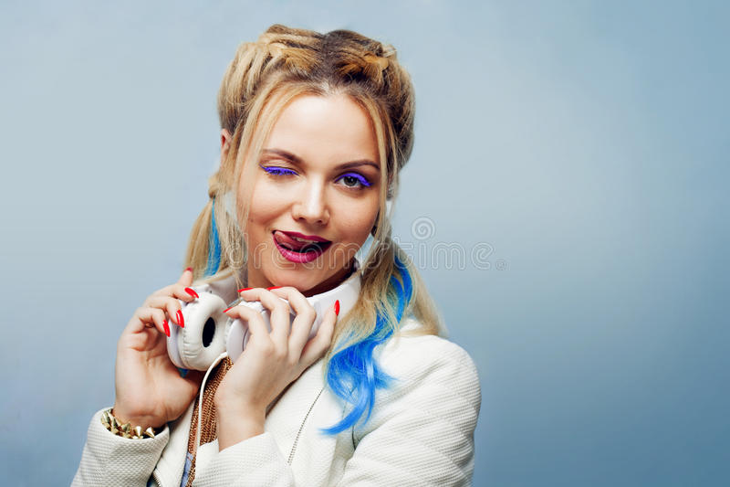 有色的子线的滑稽的女孩在她的头发 听的音乐和显示舌头 免版税图库摄影