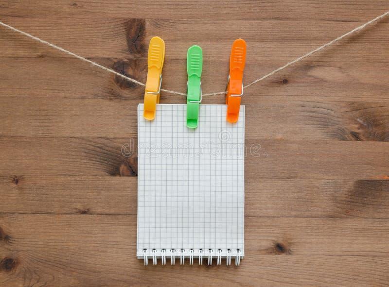 有色的晒衣夹的垂悬的笔记本在木背景 免版税库存图片