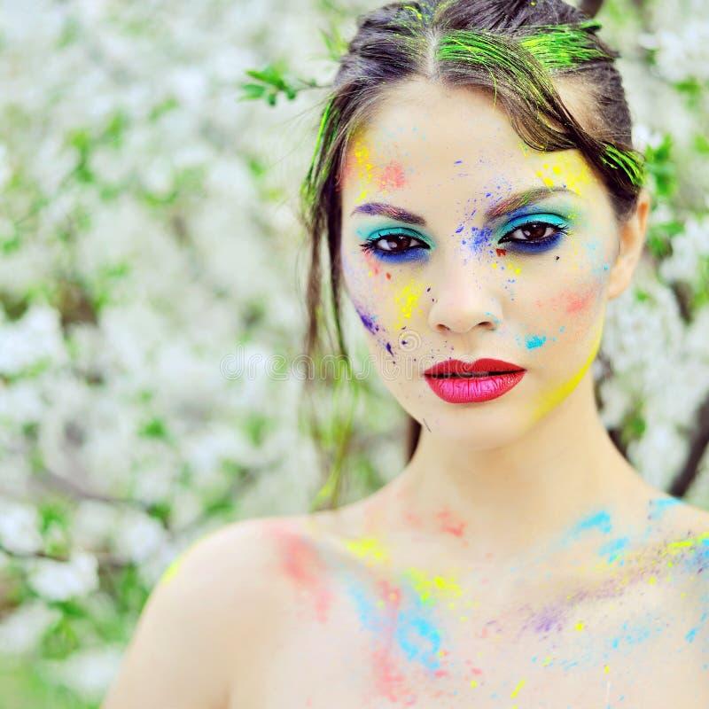 有色的油漆的美丽的妇女在室外的面孔 库存图片