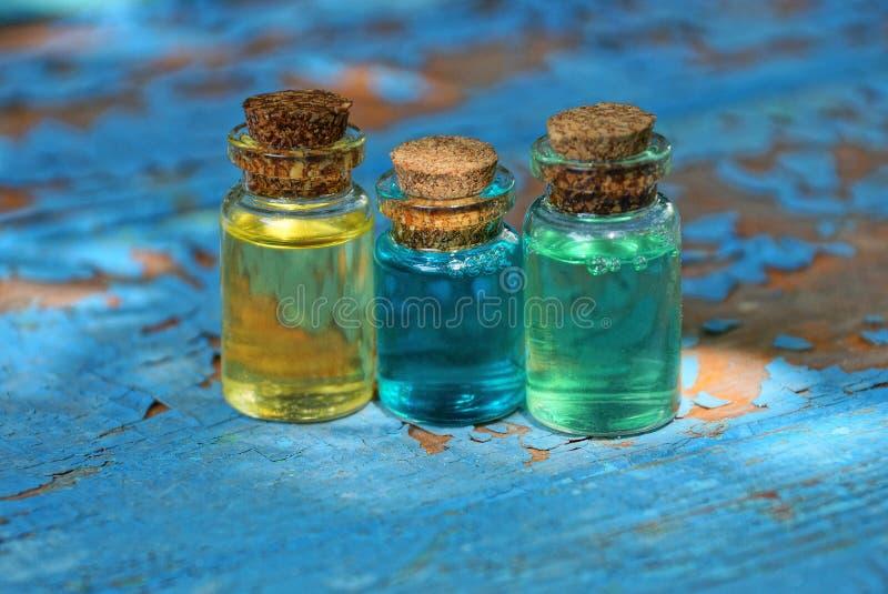 有色的油的小玻璃瓶在一张破旧的蓝色桌上站立 免版税库存照片